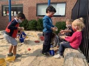 Children playing in a sandbox at German International School Boston