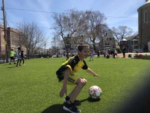 Students playing soccor on a turf field at German International School Boston
